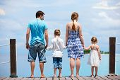 picture of family fun  - Family on wooden dock enjoying ocean view - JPG