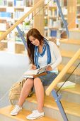 Teenage brunette student on high school library stairs reading book