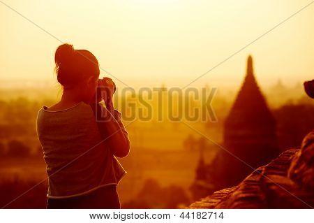 Постер, плакат: женские путешественник фотографируя храмы Bagan Мьянмы Азии на рассвете, холст на подрамнике