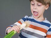 Funny kid holding leek vegetable, refusing to eat