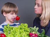 Mutter mit ihrem Sohn, der widersteht, Tomaten zu essen
