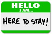 A namtag sticker with the words Hello I Am Here to Stay to symbolize dedication, persistence, stayin
