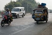 Overloaded Motorcycles And Tuk-tuks On Covered By Haze Route, Central India