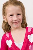 Young girl in a heart sweater making funny face