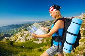 Young sporty woman standing on the peak on mountain watching on map, extreme adventure, happiness an