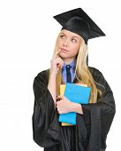 Thoughtful Young Woman In Graduation Gown With Books