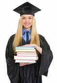 Smiling Young Woman In Graduation Gown With Stack Of Books