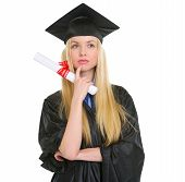 Thoughtful Young Woman In Graduation Gown With Diploma
