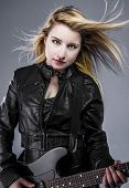 Blonde, Beautiful young woman dressed in black rock with electric guitar