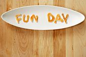 Kid's breakfast of mini pancakes with letters spelling out 'Fun Day' on wood background with copy space.