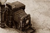 Background image of miniature vintage accordion style camera (model made from resin) on marbled tile