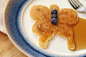 Fun butterfly shaped pancake with fresh blueberries and syrup on decorative plate.  Macro with shallow dof.