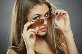 stock photo of flirtatious  - Flirtatious woman holding and looking over sunglasses with seductive eyes on grey background - JPG