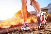 stock photo of sunrise  - athlete running sport feet on trail healthy lifestyle fitness - JPG