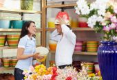 stock photo of flower shop  - mid adult couple playing with flowerpots in flower shop - JPG