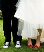 stock photo of snickers  - A young couple getting married fun choice of shoes - JPG