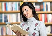 Smiling Female Student With Book In Hands In A Bookstore - Model Looking At Camera.