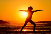 foto of breathing exercise  - Yoga exercises in beach on beautiful summer sunset alone - JPG