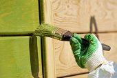 stock photo of green wall  - Hand with a paint brush painting wooden wall in green outdoor shot - JPG