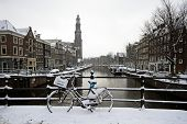 Amsterdam covered with snow with the Westerkerk in winter in the Netherlands
