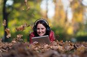 Young Woman Listening To Music In Nature