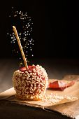 Candy apple covered in chopped nuts on rustic board