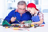 stock photo of grandpa  - Grandfather explaining to grandchild how soldering works and how to use resin - JPG