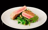 Lightly seared tuna steak and fresh salad isolated on black