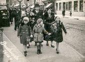 GRUDZIADZ, POLAND, CIRCA 1936 -  unidentified family with three children walking on the street - in