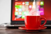 pic of hot coffee  - Laptop and a cup of coffee on a table - JPG