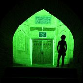Silhouette of the tourist on the background of green illuminated oriental wall with old doors. Khiva