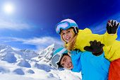 Ski, young couple has fun in mountains