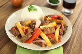 stock photo of fried onion  - Peruvian dish called Lomo Saltado made of beef tomato red onion and French fries served with rice  - JPG