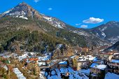 View of small french town of Tende among mountains under blue sky in winter.