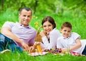 Happy family of three has picnic in park. Concept of happy family relations and carefree leisure tim