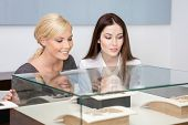 Two girls looking at showcase with jewelry at jeweler's shop. Concept of wealth and luxurious life