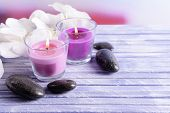 Beautiful colorful candles, spa stones and  orchid flower,on color wooden table, on light background