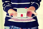 Woman holding euros bills and house model - real estate loan concept