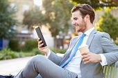 Businessman On Park Bench With Coffee Using Digital Tablet