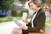 stock photo of bench  - Businesswoman On Park Bench With Coffee Using Digital Tablet - JPG