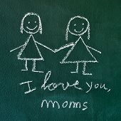 the sentence I love you, moms handwritten with chalk in a chalkboard, with a drawing of a lesbian couple