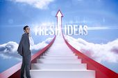 The word fresh ideas and smiling businessman standing against red steps arrow pointing up against sk