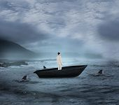 Composite image of asian businesswoman in a sailboat being circled by sharks