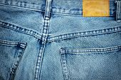 picture of denim jeans  - Blank leather jeans label sewed on a blue jeans - JPG