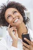 A beautiful mixed race African American girl or young woman looking up & listening to music on mp3 p