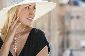 Beautiful blonde girl young woman wearing white sun hat, silver jewelry crucifix necklace and little black dress