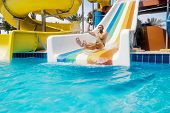 A Man Rolls Down A Hill In A Aquapark On A Bright Sunny Day