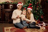 Happy smiling young family near the Christmas tree celebrate New Year. Mom dad and kid at Christmas