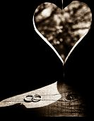 Wedding rings in heart shaped reflection on wooden background
