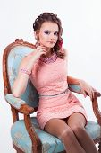 Brunette With Purple Make-up In Pink Dress Sitting On A Chair In Baroque Turquoise